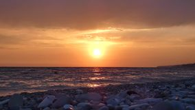 Sunset on sea beach in stormy day.. Sun closely to the horizon, water waves breaking on pebbles and stones. Summer evening. Beautiful natural landscape stock video