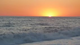 Sunset on sea beach in stormy day. Sun almost sank beyond the horizon. Water waves breaking on pebbles and stones. Summer evening. Beautiful natural landscape stock video