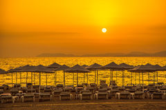 Sunset on the sea beach with sun loungers and parasols Royalty Free Stock Images
