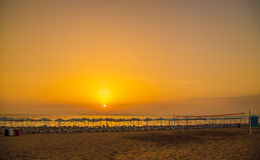 Sunset on the sea beach with sun loungers, parasols and a volley Royalty Free Stock Image