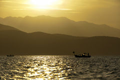 Sunset on the sea with a boat Royalty Free Stock Photos