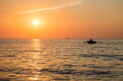 Sunset on the sea, a boat. With a rower at sunset Royalty Free Stock Images