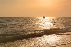Sunset on the sea and boat sailing on the horizon. Sunny path. Sunset on the sea and boat sailing on the horizon. Solar path on the waves. Romantic mood Royalty Free Stock Photos