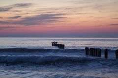 Sunset on the sea, breakwaters. Colorful sky by the sea royalty free stock images
