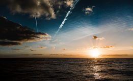Sunset at sea with calm water few clouds Stock Photos