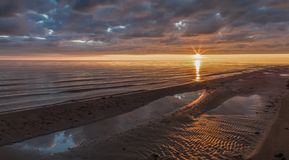 Sunset in the sea with clouds and shoreline(Rīgas jūras līcis Vitrupē). Baltic. Calm Sea at Sunset in the Gulf of Riga(Rīgas jū stock images
