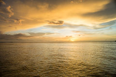 Sunset on the sea with cloudy sky background Stock Images