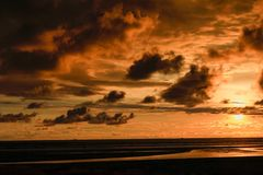 Sunset at the sea coast and cloudy stock photography