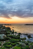 Sunset sea. The dawn at sea is always a fascinating spectacle of nature. The moss on the rocks, that rise from the water, creates a colorful texture Royalty Free Stock Photos
