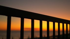 Sunset by the sea on the embankment through the bars of the fence.