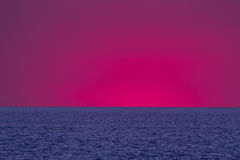 Sunset sea evening. Vibrant sunset on the sea with waves on the water surface and purple sky after sunset. and orange sky. All this makes a specific nature Stock Photos