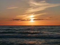 Beautiful sunset at sea. Few clouds in the sky. Sunset at sea with few clouds in the sky stock image