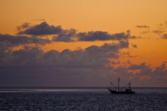 Sunset at sea with a fishing boat in the front Stock Image