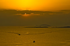 Sunset at sea, with fishing boat and nets between small islands, Sithonia Stock Image