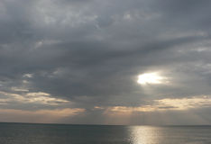 Sunset on sea with grey cloudy sky, rays of light Stock Photography