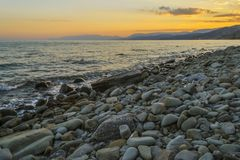 Sunset on the sea.A lot of stones on the shore. Stock Photography