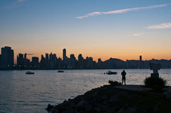 Sunset by the sea. A man stands alone observing the sunset behind the city buildings Stock Photos