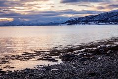 Sunset in the sea and mountain in horizon. Cloundy sky stock photo