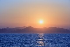 Sunset with sea and mountains Stock Image