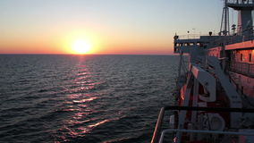 Sunset on the Sea with Moving Cargo Ferry. Big Cargo Ferry and Sunset on the Sea. Sunset orange sun over the surface of the water the sea. Full HD 1920 x 1080 stock footage