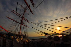 Sunset on the sea with an old sailing ship Stock Photos
