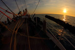 Sunset on the sea with an old sailing ship Stock Images