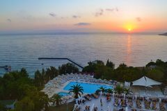 Sunset Sea and Outdoor hotel pool by night. Big Outdoor luxury blue pool at night stock photography