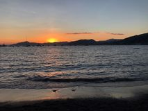 Sunset on the sea. Sunset over the sea and view of the background of a mountain range Stock Image