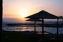 Sunset by the sea. With palm umbrellas Royalty Free Stock Image