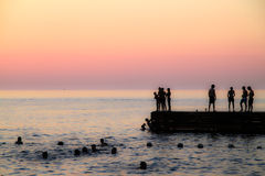 Sunset on the sea. And people Royalty Free Stock Photo