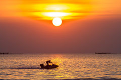 Sunset on the sea and people play water sport with light silhoue Stock Photo