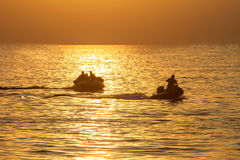 Sunset on the sea and people play water sport with light silhoue Stock Image