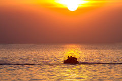 Sunset on the sea and people play water sport with light silhoue Royalty Free Stock Image