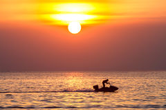 Sunset on the sea and people play water sport with light silhoue Stock Photography
