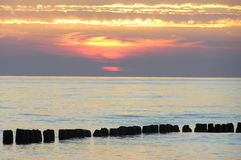 Sunset at the sea. Picture was made at Baltic Sea in Poland. The sea was very calm in that evening and sunlight made that clouds were changing colours Stock Image