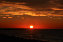 Sunset on sea with red sky and golden clouds. Full clear sunset with sun just above the horizon. The sky is red and the clouds have a golden colour Stock Photos