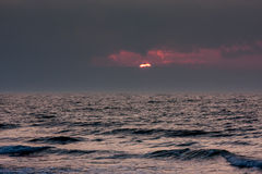 Sunset at the sea. Red sun setting between dark clouds over dark waters of the sea Royalty Free Stock Photography