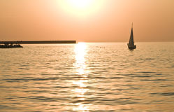 Sunset on sea and sailing boat Stock Photos