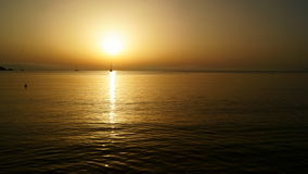 Sunset on the sea. A salingboat sleeps on water glare Royalty Free Stock Images
