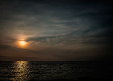 Sunset by the sea. Seascape. In the background of the setting sun. Clouds on the horizon. The image of peace and tranquility Royalty Free Stock Photos