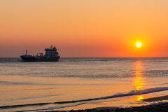 Sunset with sea and ship. In Vlissingen in Zeeland Holland. Beautiful lighting effect, waves breaking and the spray can be seen. A boat sails through the image Stock Images