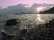 Sunset at sea shore Stock Photos