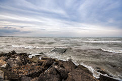Sunset at the sea shore of a beach with rocks and stormy waves, beautiful seascape at Caspian sea Absheron, Azerbaijan Novkhani. Sunset at the sea shore of a Stock Image
