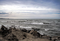 Sunset at the sea shore of a beach with rocks and stormy waves, beautiful seascape at Caspian sea Absheron, Azerbaijan Novkhani. Sunset at the sea shore of a Stock Photography
