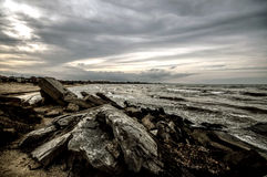 Sunset at the sea shore of a beach with rocks and stormy waves, beautiful seascape at Caspian sea Absheron, Azerbaijan Novkhani Royalty Free Stock Photo