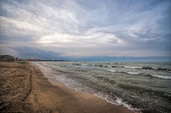 Sunset at the sea shore of a beach with rocks and stormy waves, beautiful seascape at Caspian sea Absheron, Azerbaijan Novkhani Stock Photography