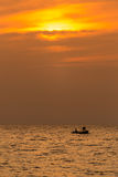 Sunset at the sea and silhouette of fisherman Royalty Free Stock Photos