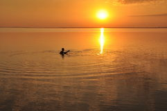 Sunset on the sea, the silhouette of a man. Beautiful sunset on the sea, the silhouette of a man - a fisherman in the water. Azov sea and estuaries, Ukraine Royalty Free Stock Image