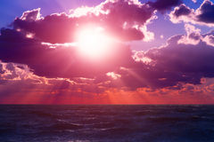 Sunset sea sky. Vibrant sunset on the sea with waves on the water surface, clouds on the sky and sun rays. All this makes a specific nature pattern Stock Photography