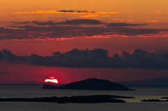 Sunset at sea, with small greek islands in background Royalty Free Stock Image
